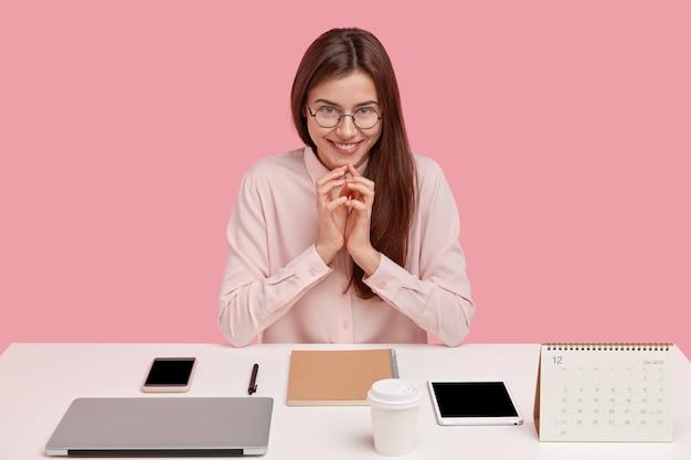 Image d'une employée de bureau européenne satisfaite étant un vrai perfectionniste, garde les mains jointes, sourit doucement