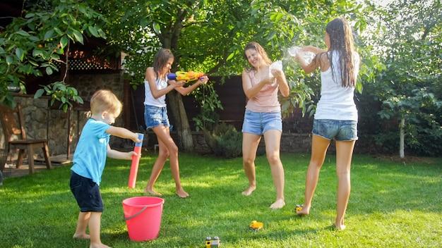 Image d'enfants joyeux et joyeux avec une jeune mère jouant avec des pistolets à eau et une maison de jardin. famille jouant et s'amusant à l'extérieur en été
