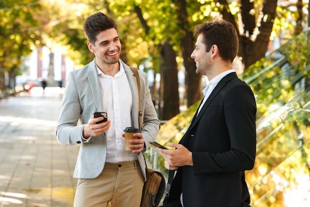 Image d'entrepreneurs masculins en costumes à l'aide de smartphone tout en marchant en plein air à travers un parc verdoyant avec du café à emporter, pendant la journée ensoleillée