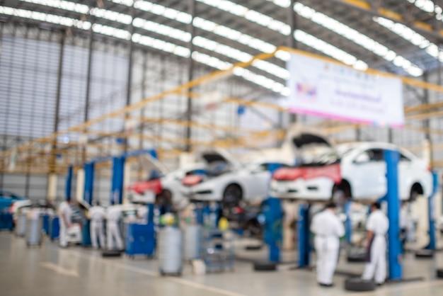 L'image est floue pendant que le mécanicien travaille dans le centre de service automobile. il y a des voitures. de nombreux clients viennent utiliser le service de vidange d'huile.