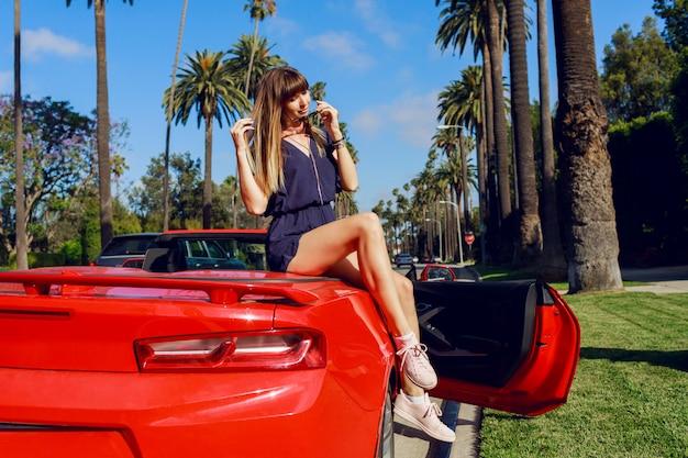 Image d'été en plein air d'une fille élégante assise sur une voiture de sport rouge de luxe, profitant de vacances à los angeles.