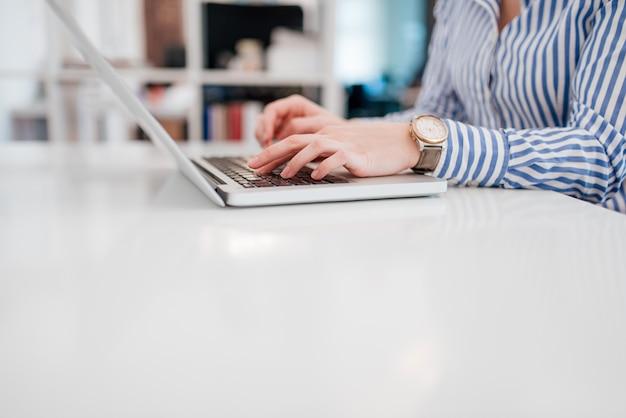 Image à faible angle de femme d'affaires en vetu en tapant sur un ordinateur portable, copiez l'espace.