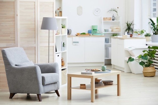 Image de fauteuil et table en bois dans le salon avec cuisine moderne