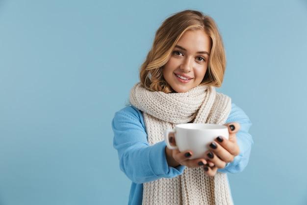 Image d'une femme adorable des années 20 enveloppée dans un foulard souriant et tenant une tasse de thé ou de café
