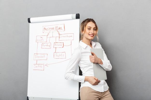 Image de femme d'affaires gaie dans des vêtements de cérémonie à l'aide de flipchart et ordinateur portable tout en faisant la présentation au bureau, isolé