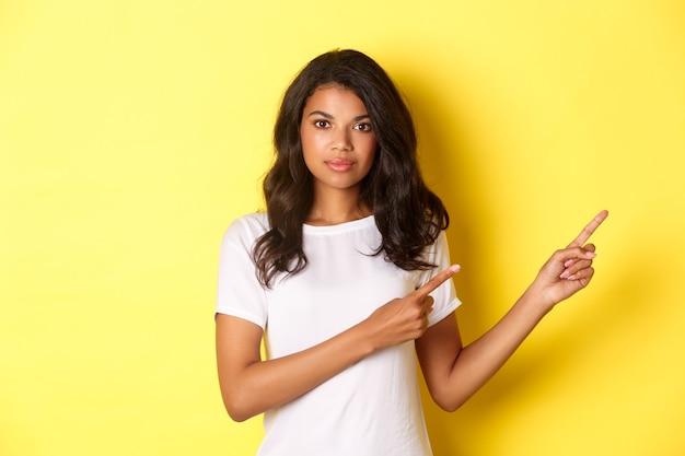 Image d'une femme afro-américaine confiante et séduisante, pointant du doigt vers la droite