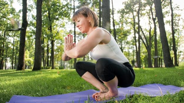 Image d'une femme d'âge moyen souriante en vêtements de fitness faisant des exercices d'étirement et de yoga. femme méditant et faisant du sport sur un tapis de fitness sur l'herbe au parc