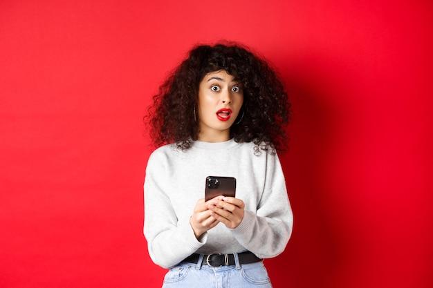 Image d'une femme assez bouclée au visage choqué, lisant un message sur un smartphone surpris, debout sur fond rouge.