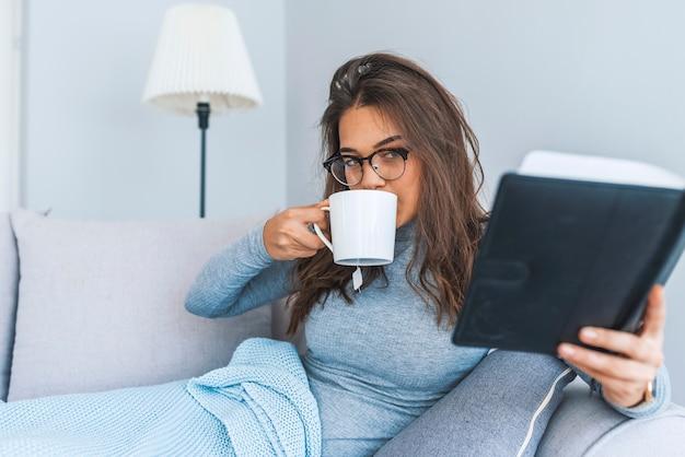 Image d'une femme assise sur le canapé et lisant un livre à la maison