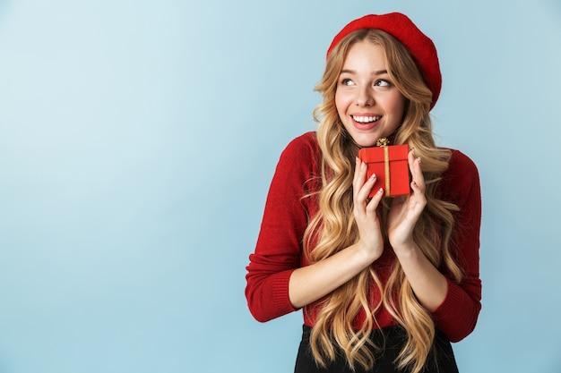 Image d'une femme blonde heureuse des années 20 portant un béret rouge tenant présent fort isolé