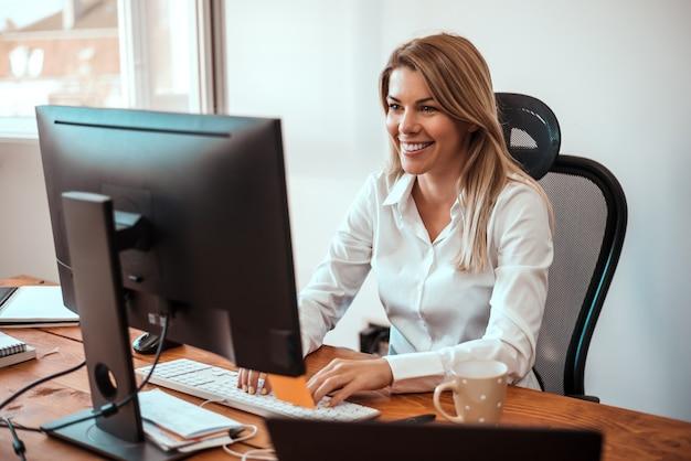 Image de femme blonde joyeuse travaillant sur ordinateur.