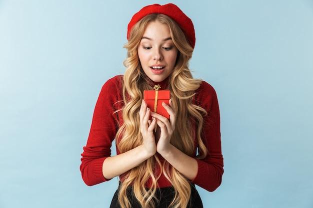 Image d'une femme blonde surprise de 20 ans portant un béret rouge tenant présent fort isolé