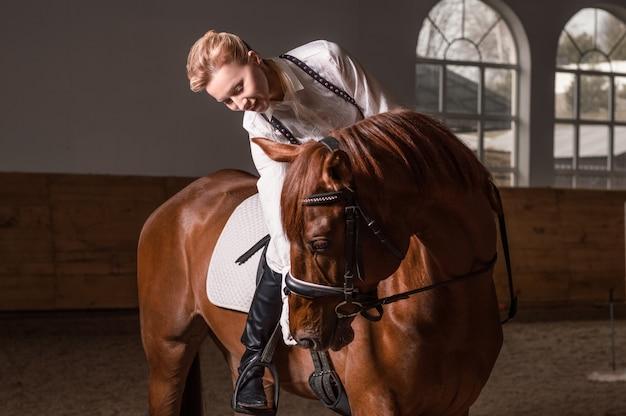 Image d'une femme chevauchant un cheval pur-sang. l'arrière-plan est une arène de course. technique mixte