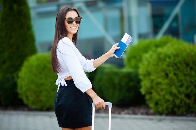 Image d'une femme européenne ayant de beaux cheveux bruns souriant tout en détenant des billets d'avion et de passeport