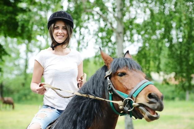 Image d'une femme heureuse assis à cheval à la ferme du village