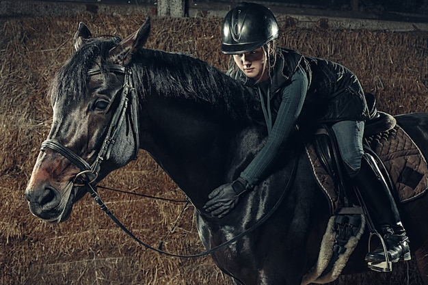Image de femme heureuse assise sur un cheval de race pure