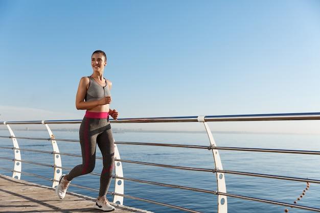 Image de femme heureuse fitness jogging le long de la promenade du bord de mer