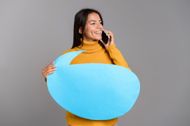 Image d'une femme heureuse posant isolé sur mur gris mur tenant la bulle de dialogue parler par téléphone.