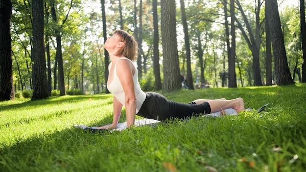 Image d'une femme heureuse souriante d'âge moyen méditant et faisant des exercices de yoga sur l'herbe dans la forêt. femme prenant soin de sa santé physique et mentale tout en pratiquant la forme physique et en s'étirant au parc