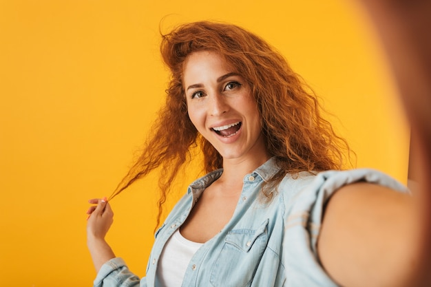 Image de femme joyeuse européenne souriant et toucher les cheveux tout en prenant selfie photo, isolé sur fond jaune