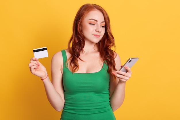 Image d'une femme magnifique aux cheveux rouges portant des vêtements décontractés, tenant une carte de crédit et un téléphone portable, regardant l'écran de l'appareil, faisant des achats en ligne.