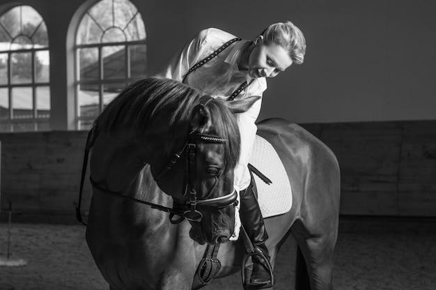 Image d'une femme montant un cheval pur-sang. l'arrière-plan est une arène de course. technique mixte