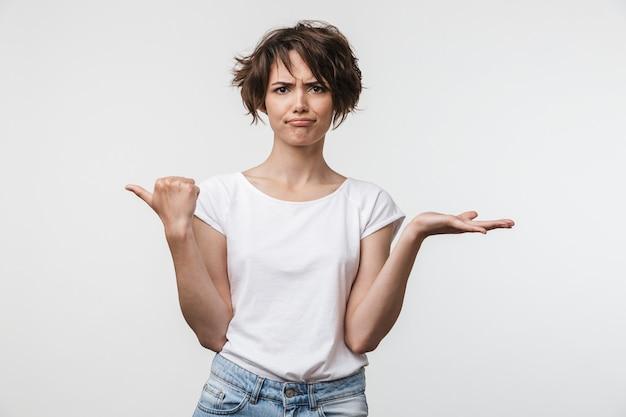 Image d'une femme perplexe aux cheveux courts en t-shirt basique pointant le doigt de côté sur un espace de copie isolé sur un mur blanc