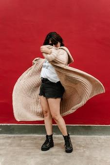 Image d'une femme qui joue avec son pull en le faisant voler. mise au point sélective d'une femme filant avec son pull tricoté à la main sur fond rouge