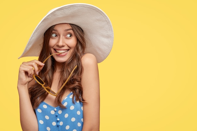 Image d'une femme rêveuse aux longs cheveux ondulés, a l'air avec une expression heureuse, a l'intention de voyager à l'étranger, tient des lunettes de soleil à la main, porte un chapeau d'été, espace libre pour le slogan sur le mur jaune