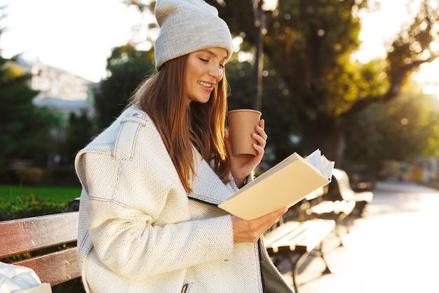Image d'une femme rousse assise sur un banc à l'extérieur tenant un livre de lecture, boire du café.