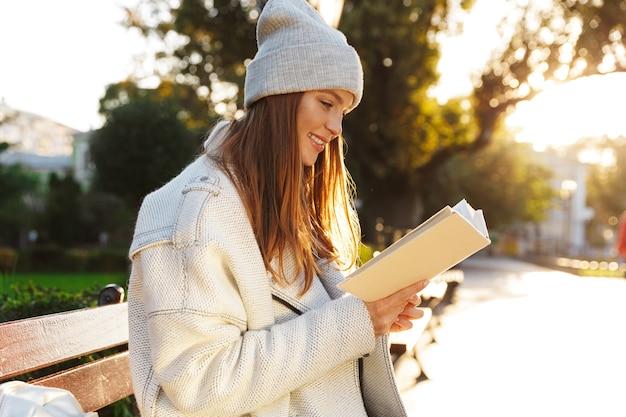 Image d'une femme rousse assise sur un banc à l'extérieur tenant un livre de lecture.