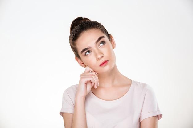 Image de femme sérieuse aux cheveux bruns en chignon avec le visage à la hausse ou rêver posant
