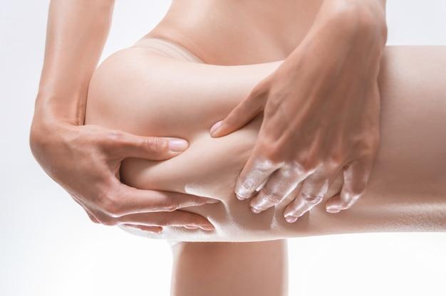 Image d'une femme serrant la peau de sa cuisse. concept cosmétique. technique mixte