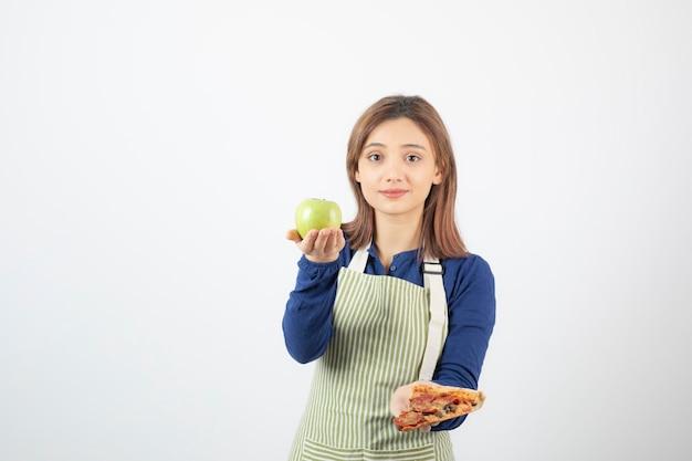 Image d'une femme en tablier essayant de choisir quoi manger pomme ou pizza