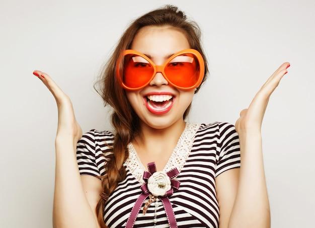 Image de fête. jeune femme espiègle avec de grandes lunettes de fête et une couronne. prêt pour du bon temps.