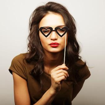 Image de fête. ludique jeune femme tenant des lunettes de fête. prêt pour du bon temps.