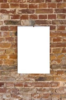 Image ou feuille vide vierge sur le mur de briques brunes.