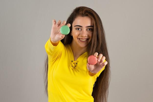 Image d'une fille adorable tenant des macarons colorés sur un mur gris.