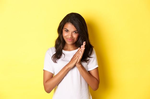 Image d'une fille afro-américaine rusée se frottant les mains et souriante ravie de savourer une bonne affaire debout