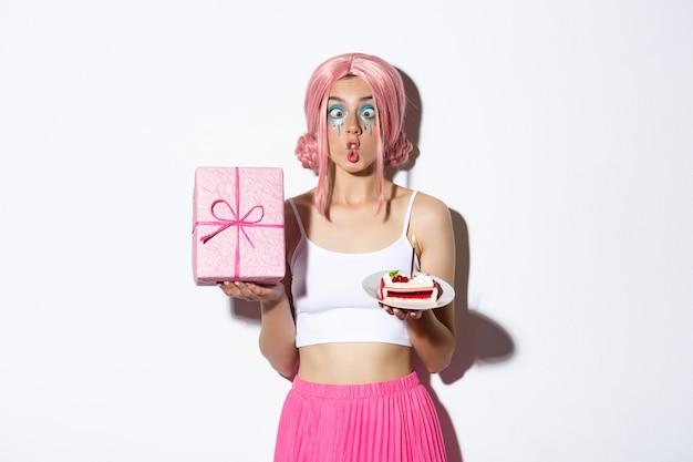 Image de fille d'anniversaire drôle faisant des grimaces idiotes, tenant un gâteau b-day et un cadeau emballé, debout.