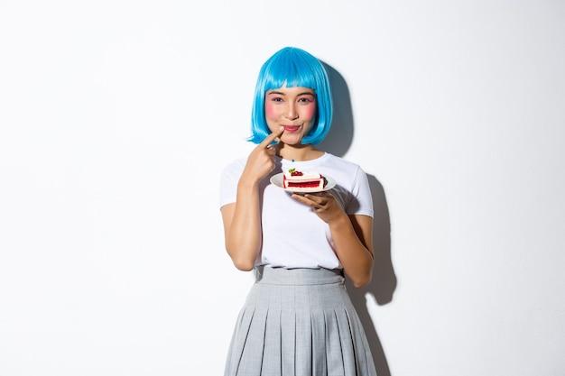 Image d'une fille asiatique coquette vous tentant d'essayer un morceau de gâteau, souriant à la caméra, debout.