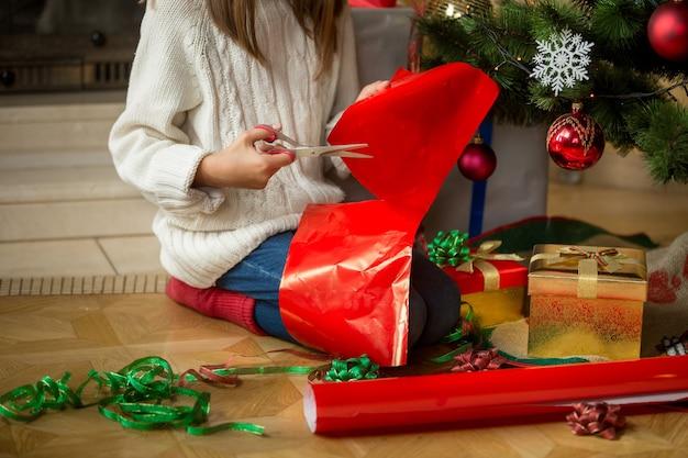 Image d'une fille assise sous un sapin de noël et coupant du papier d'emballage
