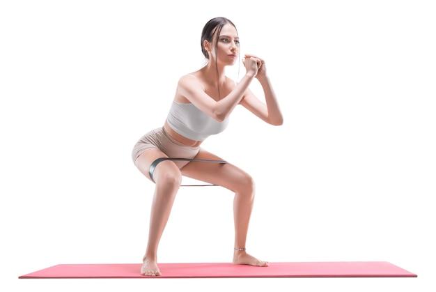 Image d'une fille athlétique accroupie avec un élastique sur un tapis. le concept de mise en forme, de pilates, d'étirement. technique mixte