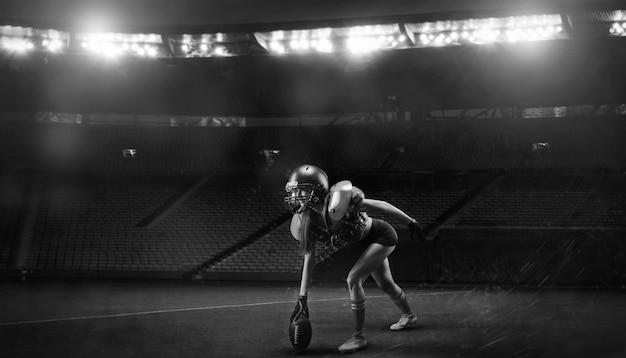 Image d'une fille dans l'uniforme d'un joueur de l'équipe de football américain se préparant à jouer le ballon au stade. notion de sport. technique mixte