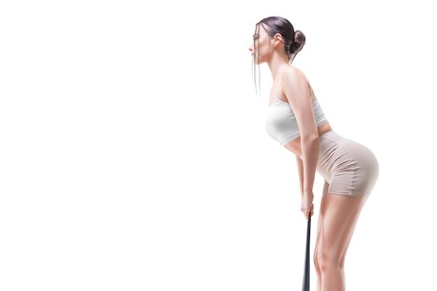 Image d'une fille sportive faisant un lifting des triceps avec une bande élastique. le concept de musculation, pilates, étirements. technique mixte
