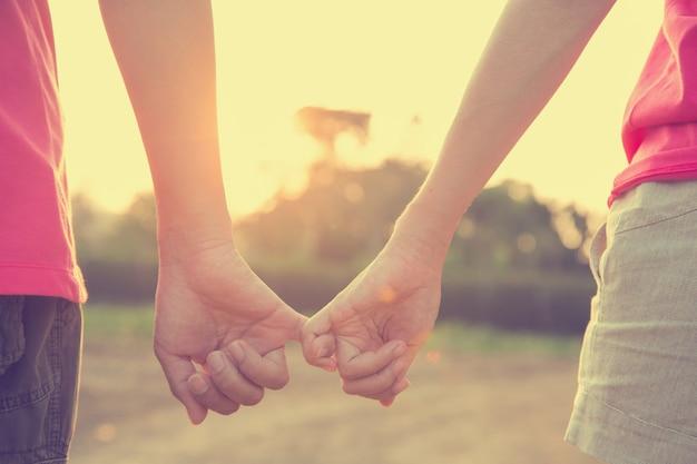 Image filtrée, couple tenant par la main dans le thème de mariage en plein air