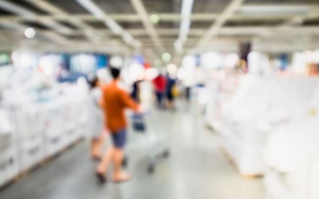 Image floue abstraite de personnes avec chariot achetant des marchandises dans le grand magasin.