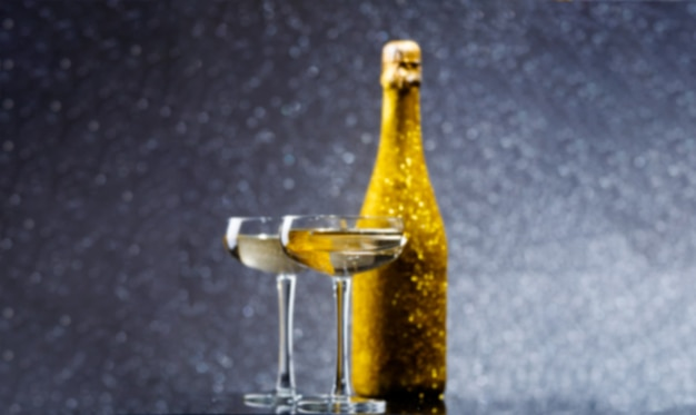 Image floue d'une bouteille de champagne dorée avec deux verres à vin
