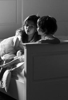 Image floue en noir et blanc d'enfants dans leur chambre pendant l'auto-isolement ou la quarantaine