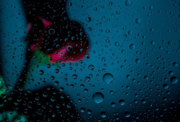 Image floue d'une rose rouge derrière un verre clair d'une fenêtre avec une goutte d'eau sur fond bleu